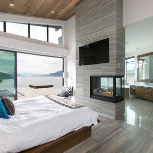 Contemporary master bedroom in Vancouver with grey walls, porcelain floors, a tile fireplace surround and a two-sided fireplace.