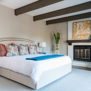 Idee per una camera matrimoniale tradizionale di medie dimensioni con pareti beige, pavimento in legno massello medio, camino classico, cornice del camino in mattoni e pavimento marrone