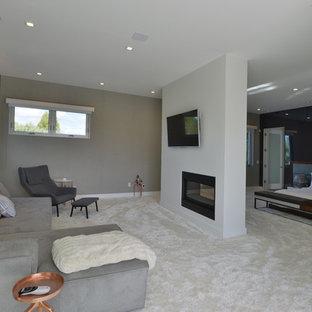 Diseño de dormitorio principal, moderno, grande, con paredes grises, moqueta, chimenea tradicional y marco de chimenea de metal