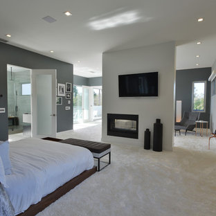 This is an example of a large modern master bedroom in Los Angeles with grey walls, carpet, a metal fireplace surround and a two-sided fireplace.