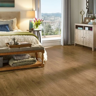 Example of a large transitional master medium tone wood floor and brown floor bedroom design in Other with beige walls and no fireplace