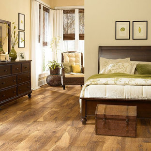 Foto de dormitorio principal, exótico, de tamaño medio, sin chimenea, con paredes beige, suelo marrón y suelo laminado