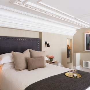 Classic guest bedroom in London with beige walls, carpet and beige floors.