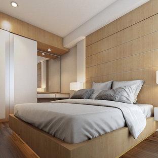 Immagine di una piccola camera matrimoniale contemporanea con pareti marroni, pavimento in laminato, camino sospeso, cornice del camino in mattoni e pavimento marrone
