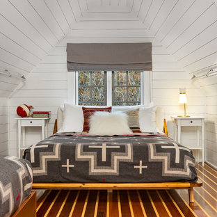 This is an example of a contemporary bedroom in New York with white walls, medium hardwood floors and brown floor.