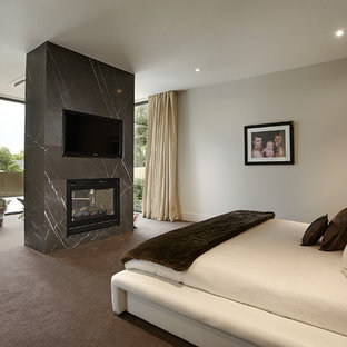 Large contemporary bedroom in Melbourne with white walls, carpet, a stone fireplace surround and a two-sided fireplace.