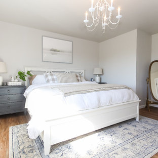 This is an example of a small transitional master bedroom in Seattle with grey walls, vinyl floors and brown floor.