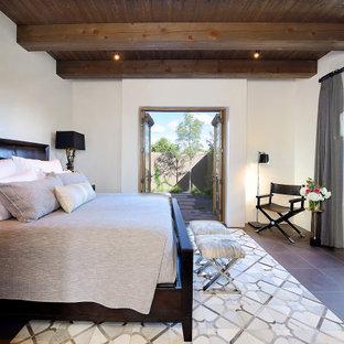 Imagen de dormitorio principal, de estilo americano, de tamaño medio, con paredes beige, suelo de pizarra y suelo marrón