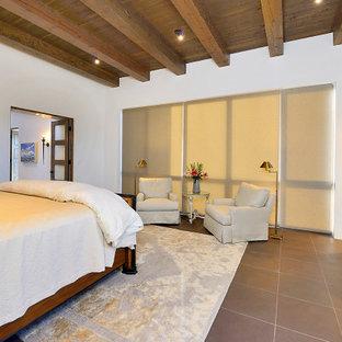 Diseño de dormitorio principal, de estilo americano, grande, con paredes blancas, suelo de pizarra, chimenea lineal, marco de chimenea de yeso y suelo marrón