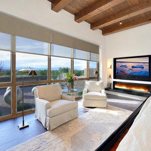 Ejemplo de dormitorio principal, de estilo americano, grande, con paredes blancas, suelo de pizarra, chimenea lineal, marco de chimenea de yeso y suelo marrón