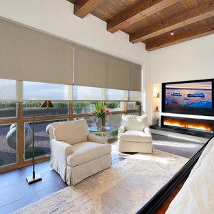 Imagen de dormitorio principal, de estilo americano, grande, con paredes blancas, suelo de pizarra, chimenea lineal, marco de chimenea de yeso y suelo marrón