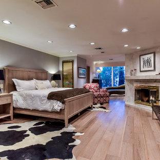 Foto de dormitorio principal, retro, grande, con paredes grises, suelo de madera clara, chimenea de esquina, marco de chimenea de baldosas y/o azulejos y suelo beige