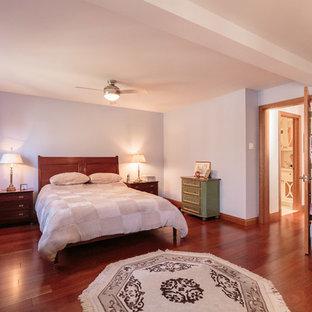 Cette photo montre une grande chambre parentale chic avec un mur bleu et un sol en bois brun.