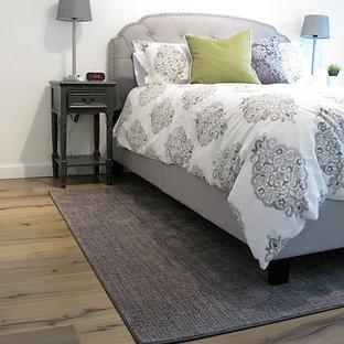Cette photo montre une chambre d'amis chic de taille moyenne avec un mur blanc, sol en stratifié, aucune cheminée et un sol marron.