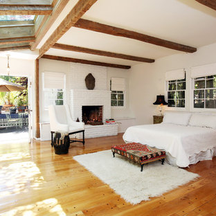 Large tuscan master medium tone wood floor bedroom photo in Los Angeles with white walls, a standard fireplace and a brick fireplace