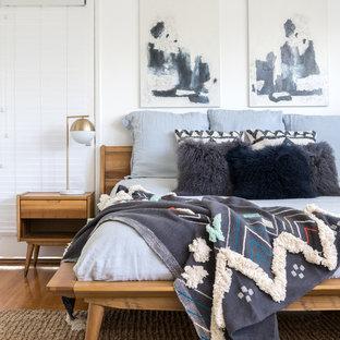 他の地域の大きいミッドセンチュリースタイルのおしゃれな主寝室 (白い壁、無垢フローリング、茶色い床) のインテリア