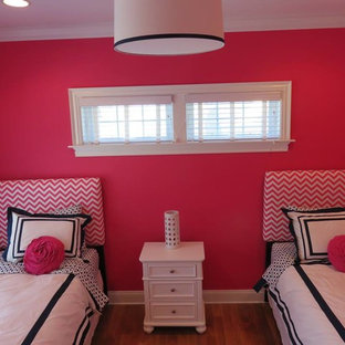 Mid-sized beach style medium tone wood floor bedroom photo in New York with pink walls and no fireplace