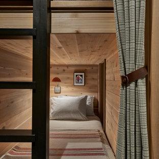 Modelo de habitación de invitados rural, de tamaño medio, con paredes beige, suelo de pizarra y suelo negro