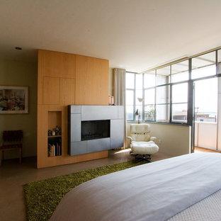 Ispirazione per una camera matrimoniale minimalista con pareti beige, camino sospeso, cornice del camino in pietra e pavimento marrone
