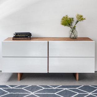 Imagen de habitación de invitados actual, pequeña, con paredes blancas y suelo de cemento