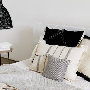 Imagen de dormitorio tipo loft, minimalista, grande, con paredes blancas, suelo de cemento, chimenea tradicional y marco de chimenea de yeso