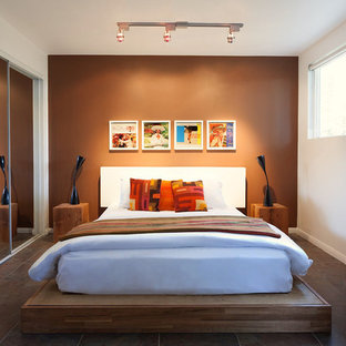 Mid-sized guest bedroom in Los Angeles with brown walls, terra-cotta floors and no fireplace.