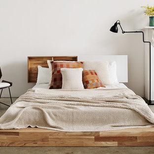 Diseño de dormitorio moderno, grande, con paredes blancas, suelo de cemento, chimenea tradicional y marco de chimenea de madera