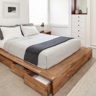 ロサンゼルスの小さいコンテンポラリースタイルのおしゃれな客用寝室 (白い壁、コンクリートの床) のインテリア