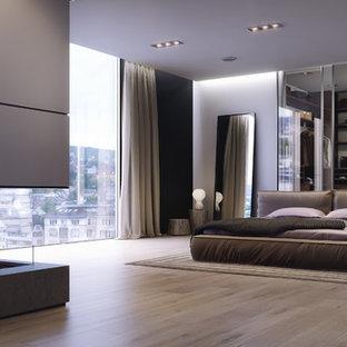 На фото: большая хозяйская спальня в стиле модернизм с светлым паркетным полом, двусторонним камином и фасадом камина из камня с