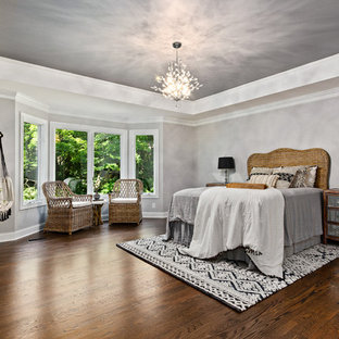 This is an example of a mid-sized mediterranean master bedroom in Kansas City with grey walls and dark hardwood floors.