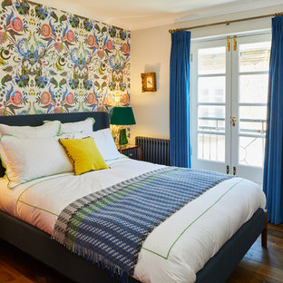 Design ideas for an eclectic bedroom in London with multi-coloured walls, medium hardwood flooring and brown floors.