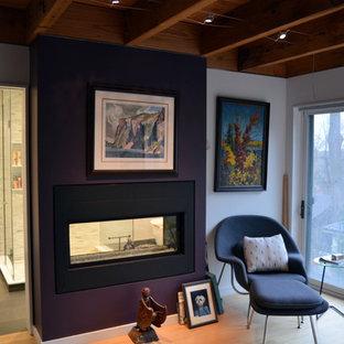 Ispirazione per una camera matrimoniale minimal di medie dimensioni con pareti viola, parquet chiaro, camino bifacciale e cornice del camino in metallo