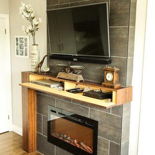 Ejemplo de dormitorio principal, clásico renovado, de tamaño medio, con paredes grises, suelo de madera en tonos medios, chimenea lineal, marco de chimenea de baldosas y/o azulejos y suelo marrón