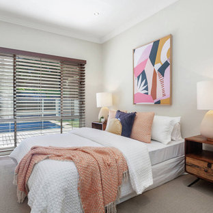This is an example of a contemporary guest bedroom in Central Coast with grey walls, carpet, no fireplace and beige floor.