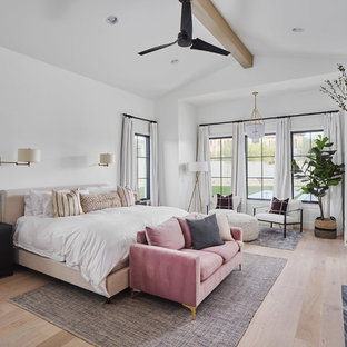 Example of a large farmhouse master light wood floor and beige floor bedroom design in Phoenix with white walls, a standard fireplace and a stone fireplace