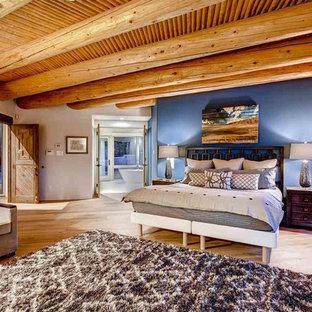 アルバカーキの広いサンタフェスタイルのおしゃれな寝室 (青い壁、無垢フローリング)