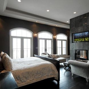 Immagine di una grande camera matrimoniale chic con pareti nere, pavimento in legno verniciato, camino sospeso, cornice del camino in pietra e pavimento nero