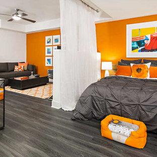 Modelo de dormitorio minimalista, pequeño, con parades naranjas y suelo de madera oscura