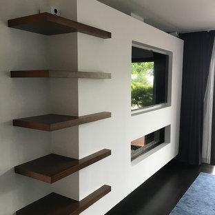 Ejemplo de dormitorio principal, moderno, de tamaño medio, con paredes blancas, suelo de madera oscura, chimenea lineal, marco de chimenea de yeso y suelo negro