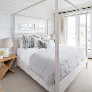 Idée de décoration pour une chambre marine avec un mur blanc, un sol en bois clair et un sol beige.