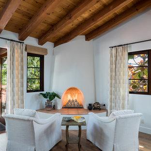 Esempio di una piccola camera matrimoniale costiera con pareti bianche, pavimento in legno massello medio, camino ad angolo e cornice del camino in intonaco