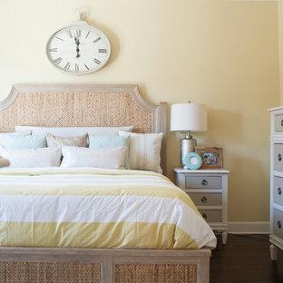 Diseño de dormitorio principal, tropical, de tamaño medio, con paredes amarillas y suelo de madera oscura