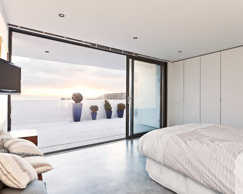 Example Of A Trendy Concrete Floor Bedroom Design In Hampshire