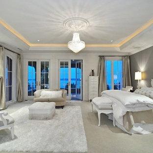 Пример оригинального дизайна: огромная хозяйская спальня в стиле современная классика с серыми стенами, ковровым покрытием, стандартным камином и фасадом камина из дерева