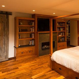 Imagen de dormitorio principal, rural, de tamaño medio, con paredes beige, suelo de madera en tonos medios, chimenea lineal y marco de chimenea de baldosas y/o azulejos