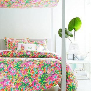 Immagine di una camera da letto tropicale con pareti bianche e pavimento in legno verniciato