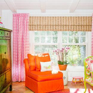 Modelo de dormitorio tropical, sin chimenea, con paredes blancas y suelo de baldosas de terracota