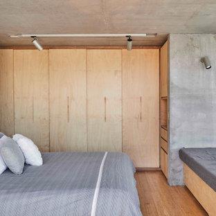 Réalisation d'une chambre parentale minimaliste de taille moyenne avec un sol en bambou, un mur gris et un sol beige.