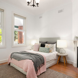 This is an example of a small transitional bedroom in Sydney with medium hardwood floors, a corner fireplace, white walls, brown floor and a plaster fireplace surround.