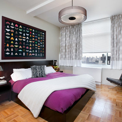 Example of a mid-sized trendy guest light wood floor bedroom design in New York with gray walls and no fireplace